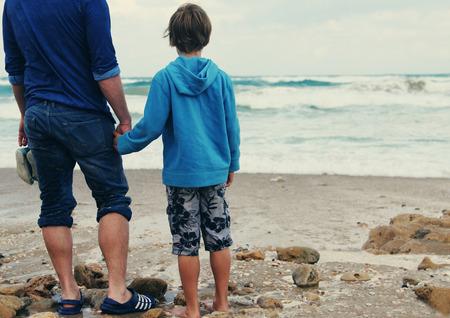 vader en zoon lopen op het strand Stockfoto