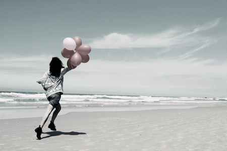 beautiful woman holding red balloons and walking on seaside photo