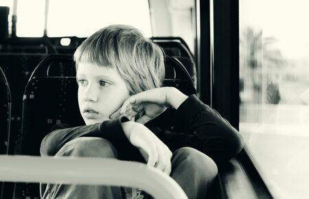 autistic: Cute autistic boy siting in empty bus Stock Photo