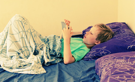 7 anni ragazzo si trova nel letto e gioca con un computer portatile Archivio Fotografico