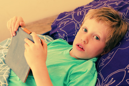 7 year old: 7 year old boy lies in bed and plays with a laptop Stock Photo