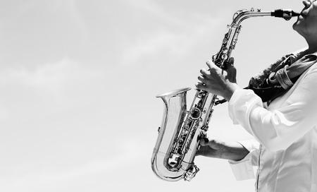 saxofón: Saxofonista de juego en el saxofón en el fondo de cielo azul Foto de archivo