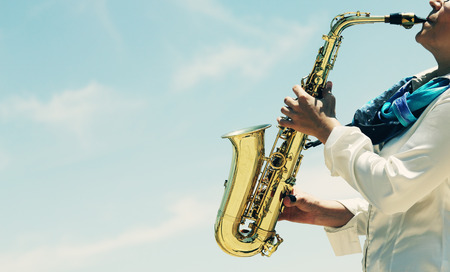 青空をバックにサックスの演奏のサクスホーン奏者