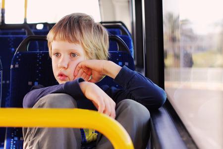 alone boy: Cute autistic boy sitting in empty bus