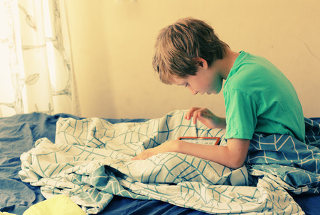 7 year old boy lies in bed and plays with a laptop photo