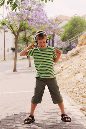 autistic: Cute autistic boy with headphones dancing in the street