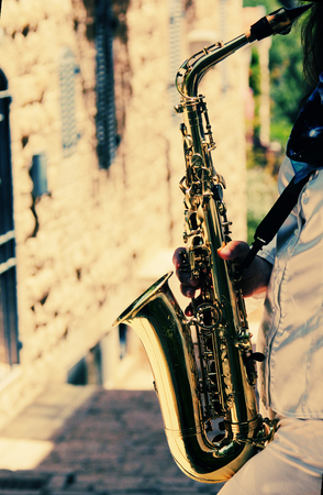 saxophonist: Saxophonist playing on saxophone on blue sky background