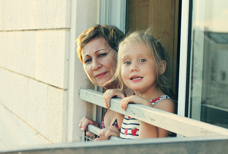 grandchild: grandmother with her grandchild looking from the window