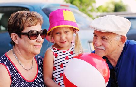 grandchild: grandparents with grandchild outdoors