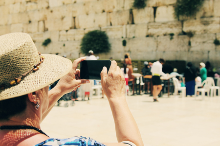 western wall: elderly woman takes a picture of the Western Wall and Jerusalem