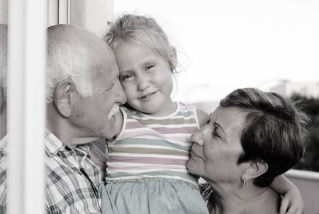 4 years old: grandfather and grandmother holding  4 years old granddaughter Stock Photo