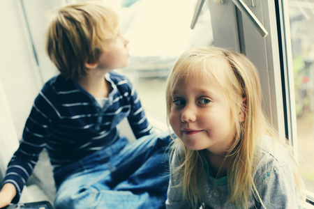 autism: Sister and brother are sitting near the window