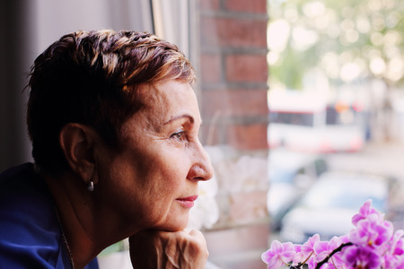 60 years old woman looking to the window Stock fotó