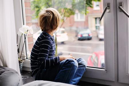 kinder spielen: 7 Jahre alter Junge sitzt am Fenster und blickte auf die Straße