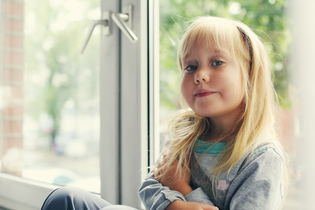 5 years old: Portrait of 5 years old girl lsitting near the window Stock Photo