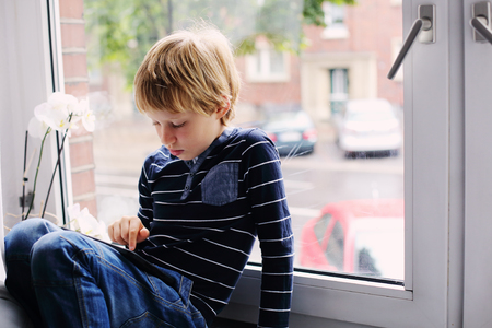 7 year old: 7 year old boy sitting near the window and playing tablet Stock Photo