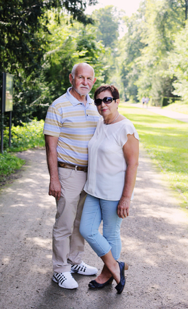 active life: senior couple walking together in summer park