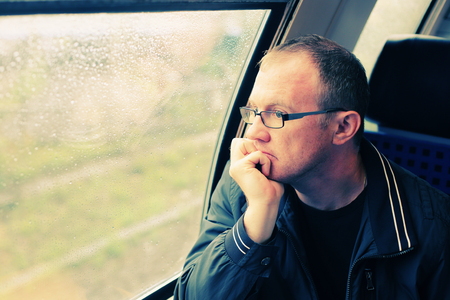 40 years old man: Handsome 40 years old man looking to the window in the train