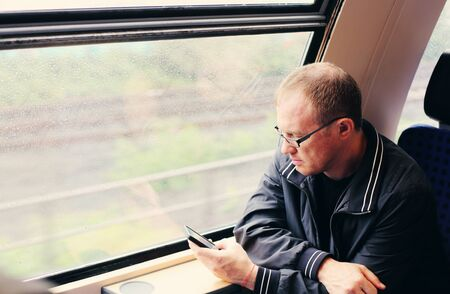 40 years old man: Handsome 40 years old man holding smartphone and traveling in the train