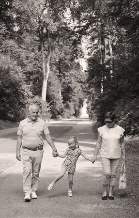 granny and grandad: Grandparents With Grandchild walking together in the park Stock Photo