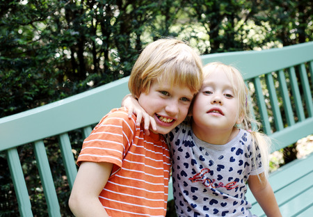 Portrait of happy girl with her autistic brother outdoors Stock Photo