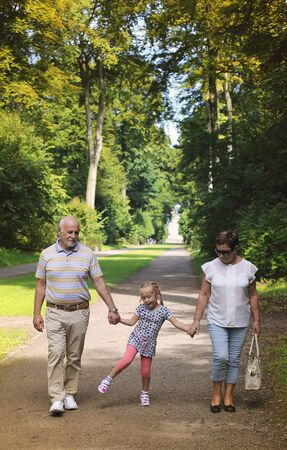 grandchild: Grandparents With Grandchild walking together in the park Stock Photo