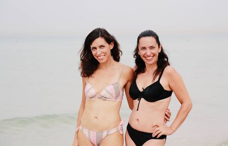 35 years: two beautiful 35 years old women standing on the beach