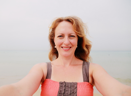 35 years: beautiful 35 years old woman standing on the shore of the beach. selfie