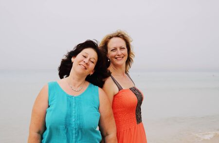 35 years old: two beautiful 35 years old women standing on the beach