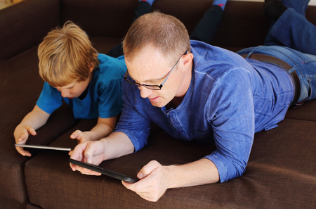 an adult person: father and son playing games on tablets