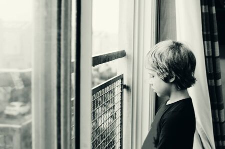 8 years: Cute 8 years old autustic boy looking at the rain