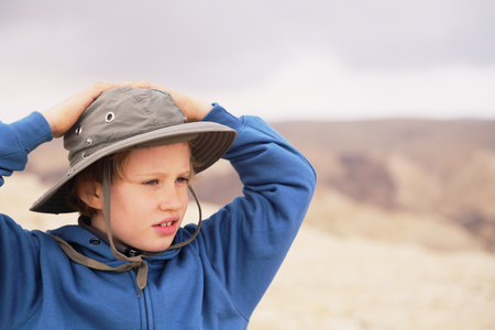 8 years old: Cute 8 years old boy hiking in desert Stock Photo