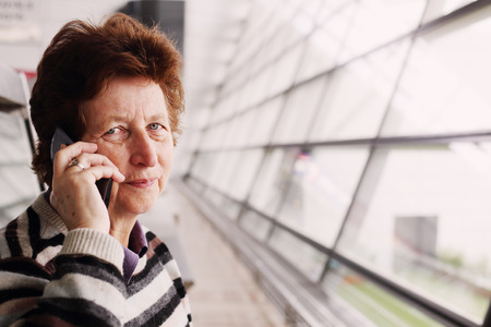horizontal haircut: Portrait of beautiful 70 years old woman with mobile phone Stock Photo