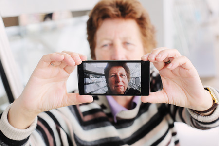 using mobile phone: Senior woman taking selfy picture on mobile device