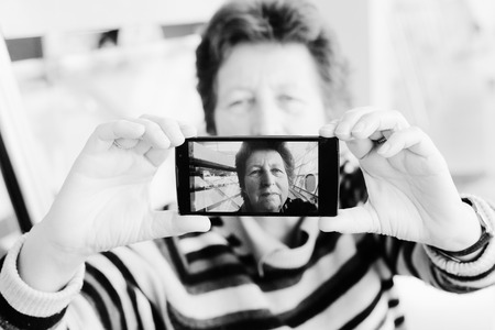 selfy: Senior woman taking selfy picture on mobile device