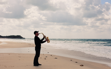 saxophonist: Saxophonist playing on saxophone on blue sky and sea background