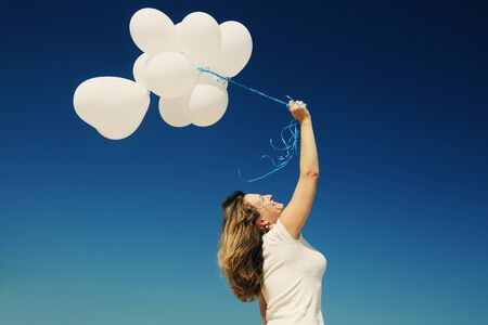 sky brunch: Beautiful redhead woman holding pink balloons Stock Photo