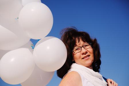 sky brunch: woman holding white balloons on seaside