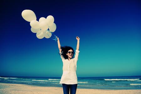 woman holding white balloons on seaside