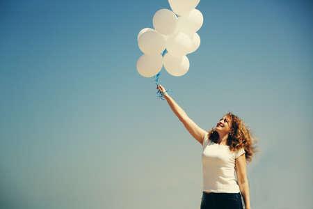 beautiful redhead: Beautiful redhead woman holding white balloons Stock Photo