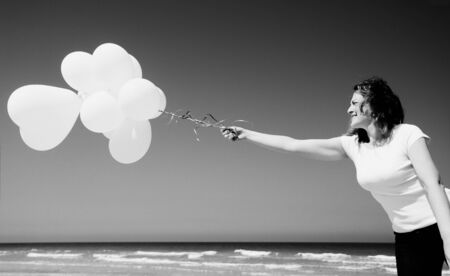sky brunch: Beautiful redhead woman holding white balloons Stock Photo