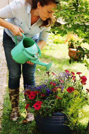 Porträt von schönen 40 Jahren alten Frauen, die am sonnigen Tag im Garten im Garten arbeiten
