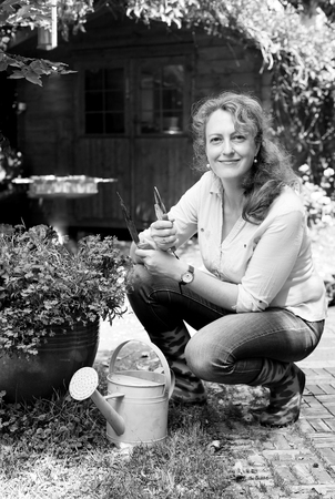 middle easter: Portrait of beautiful 40 years old woman gardening on sunny day in the garden