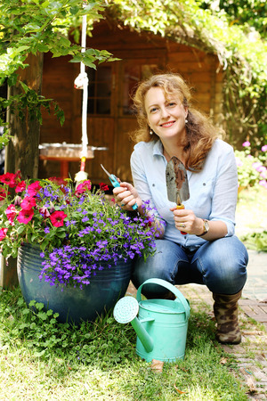 40 years old: Portrait of beautiful 40 years old woman gardening on sunny day in the garden