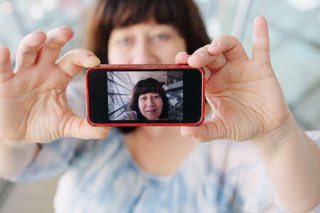 selfy: Beautiful 45 years old woman taking selfy picture on mobile device Stock Photo