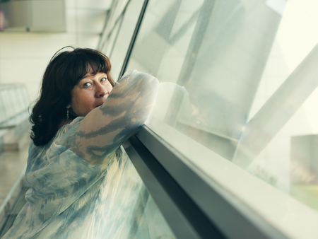 40 years old: Portrait of beautiful 40 years old woman standing near the window