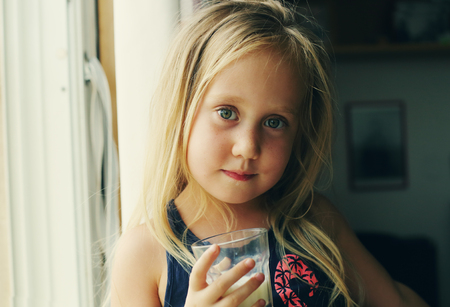 5 years: 5 years old girl holding glass of milk