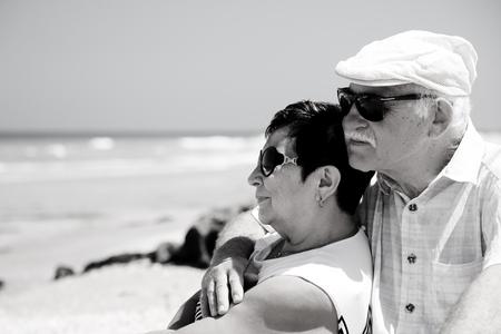 senior couple sitting on the beach Stock Photo