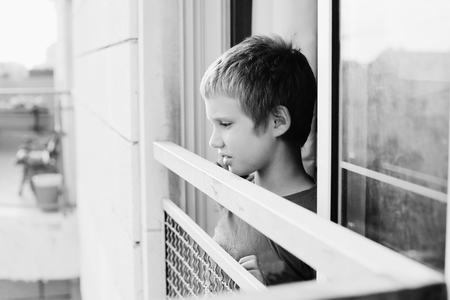 8 years old: Cute 8 years old autustic boy looking at the street Stock Photo