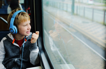 8 years old: Cute 8 years old boy looking through the window in the train